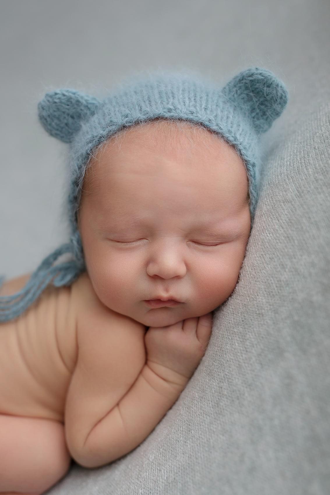 Focení miminka s modrou čepičkou na dece