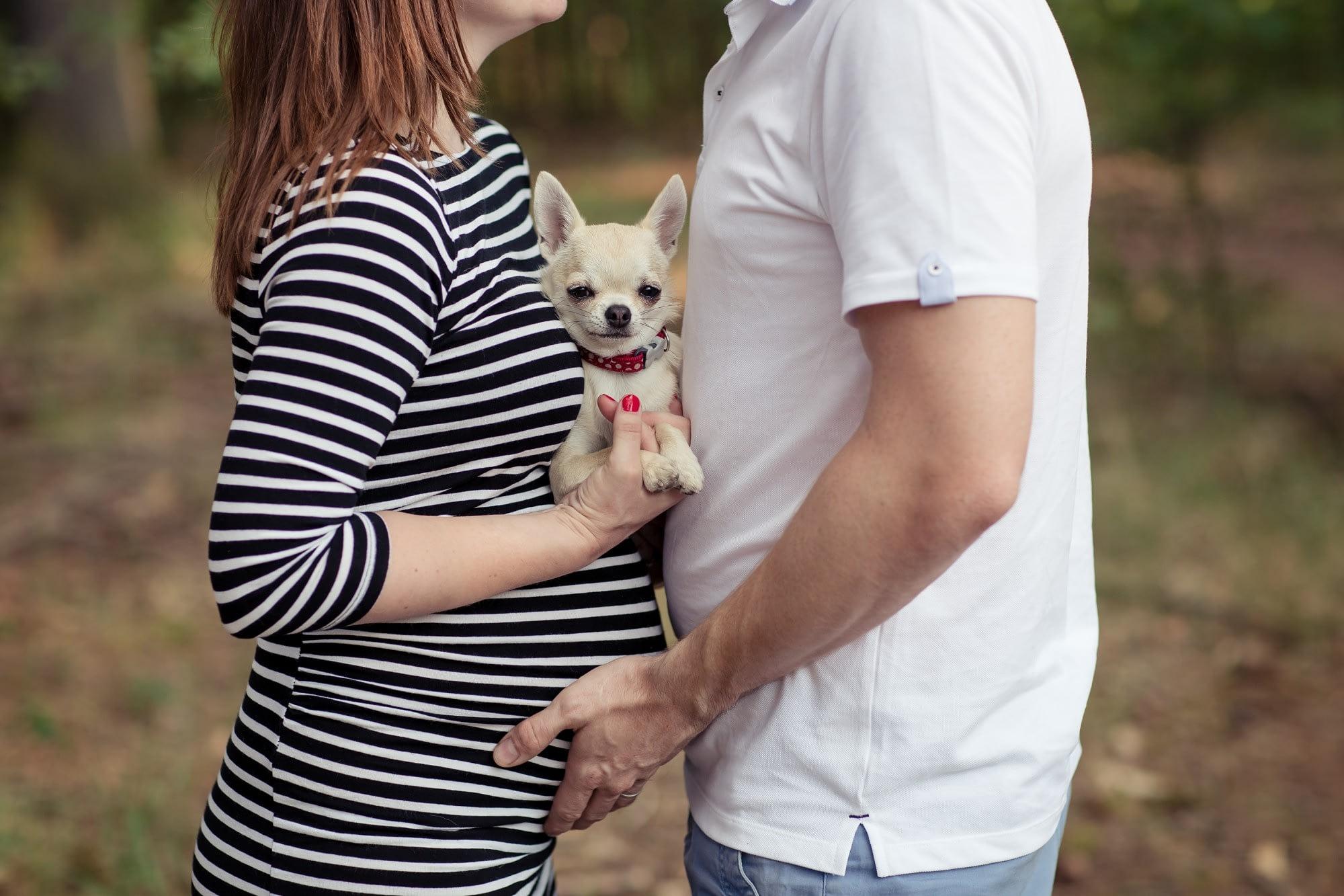 Těhulka s partnerem a psem se fotí v přírodě