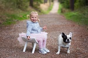 Foceni deti v prirode, Kunraticky les, holcicka sedi na bile zidlicce vedle pes buldocek